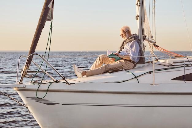 Uomo anziano rilassato che legge un libro mentre è seduto sul lato della barca a vela o sul ponte di uno yacht che galleggia dentro