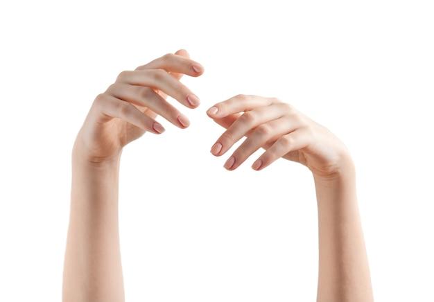 Rilassate due mani femminili con unghie beige manicure su bianco