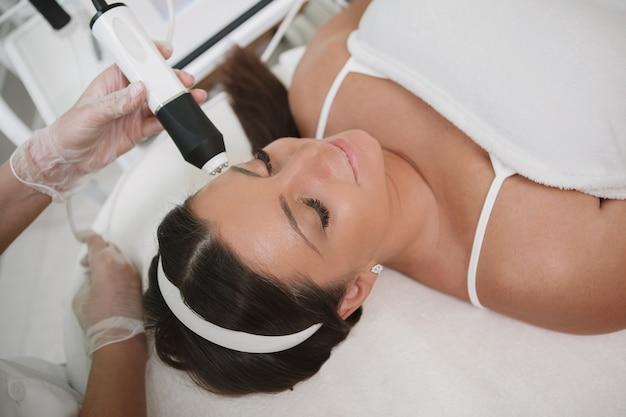 Donna rilassata che gode del trattamento facciale professionale dal cosmetologo