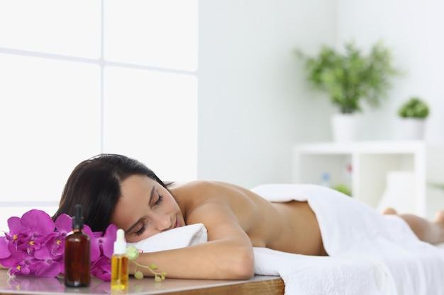 La donna rilassata si trova nel centro termale sul lettino da massaggio.