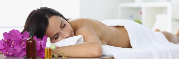 La donna rilassata si trova nel centro termale sul lettino da massaggio