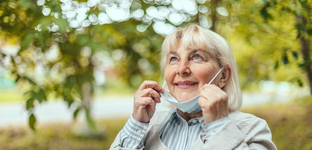 La donna rilassata si toglie la maschera medica protettiva dal viso per respirare