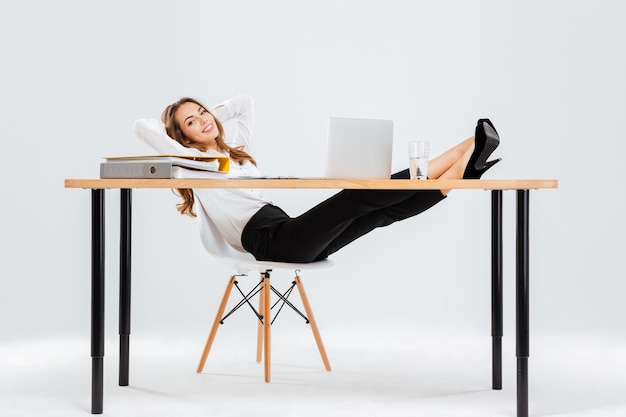 Rilassata giovane imprenditrice seduta e rilassante con le gambe sul tavolo su sfondo bianco