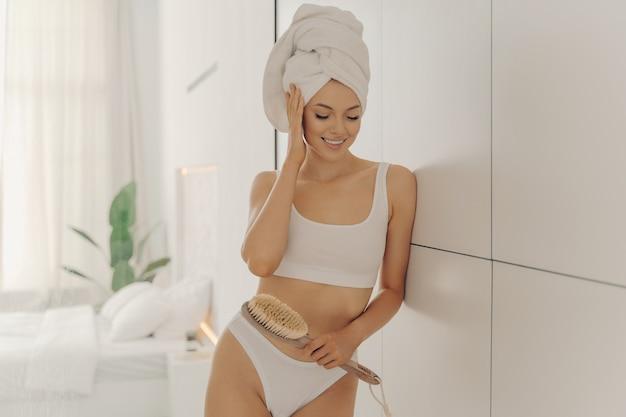 La giovane modella caucasica rilassata indossa un asciugamano avvolto sulla testa dopo i trattamenti per la cura del corpo a casa