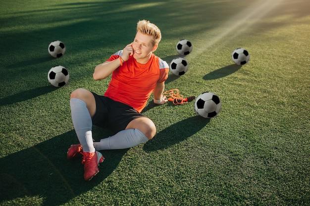 Giovane giocatore rilassato sdraiato sul prato e parla al telefono