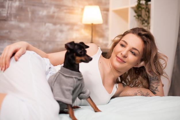 Giovane donna rilassata e il suo cane che trascorrono del tempo a letto. donna attraente in pigiama.