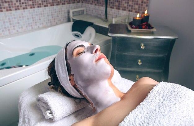 Rilassata giovane donna che riposa sdraiata con maschera facciale di argilla nella spa. medicina, sanità e concetto di bellezza.