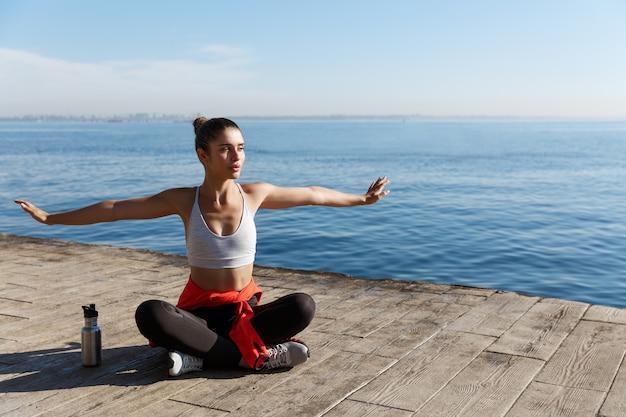 Giovane donna rilassata che si siede sul molo in legno e guardando il mare, facendo esercizi di yoga