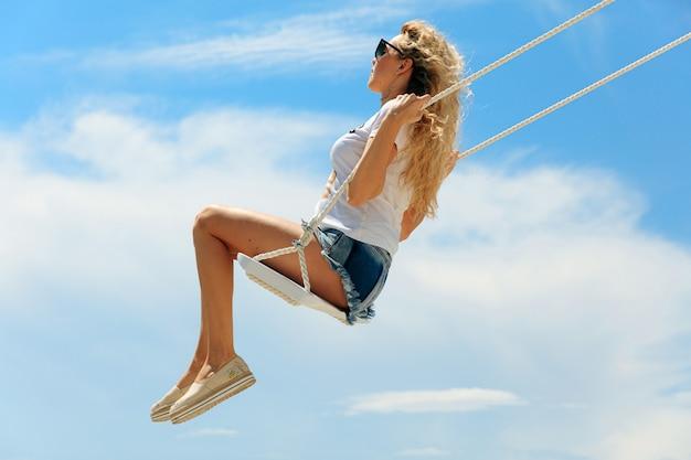 Giovane donna rilassata che indossa abiti estivi alla moda che oscillano in alto vicino al lago durante la stagione calda. bella bionda in occhiali da sole godendo di attività all'aperto.