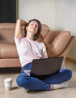 Giovani donne rilassate sedute sul pavimento con laptop e caffè per andare vicino al divano di casa