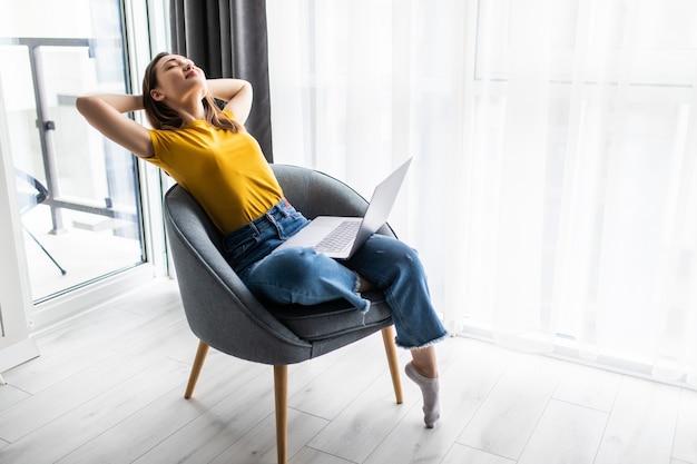 Rilassante donna asiatica seduta comoda nella poltrona del divano