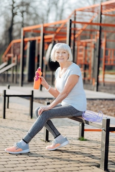 Rilassarsi in panchina. allerta donna sottile in possesso di una bottiglia di succo di frutta e rilassarsi durante l'allenamento