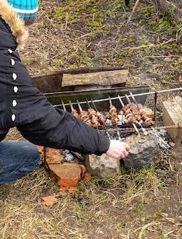 Rilassarsi in giardino nella natura, spiedini succosi di capra selvatica su spiedini, trofeo del cacciatore, cucinare spiedini sul fuoco, l'uomo accende gli spiedini sul fuoco