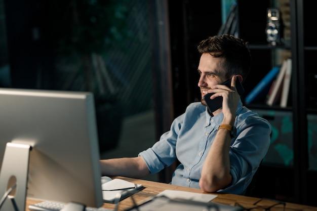 Uomo di rilassamento che parla sul telefono in ufficio