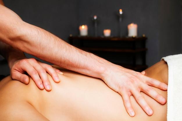 Massaggio rilassante con olio. mani del massaggiatore. schiena delle donne.
