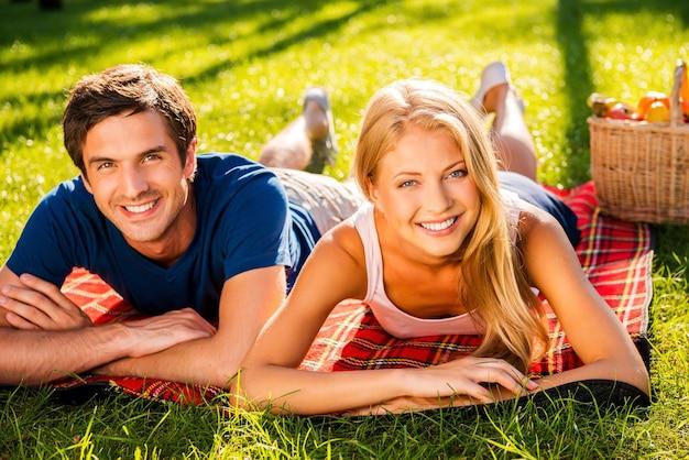 Rilassarsi nel parco insieme. felice giovane coppia di innamorati che si rilassano nel parco insieme sdraiati su una coperta da picnic
