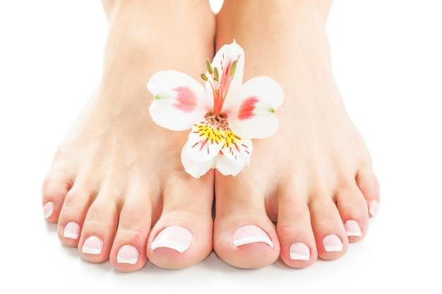 Manicure e pedicure rosa rilassante con un fiore di orchidea