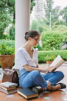 Tempo di relax di una studentessa giovane donna che legge alcuni libri