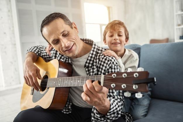 Rilassarsi insieme. uomo dai capelli scuri allerta attraente che sorride e che suona la chitarra e suo figlio che lo abbraccia
