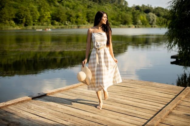 Rilassante giovane donna in piedi sul molo di legno al lago calmo
