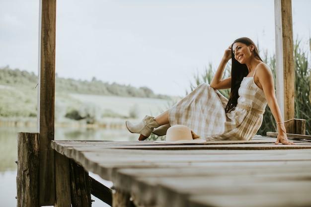 Rilassante giovane donna sul molo di legno al calmo lago