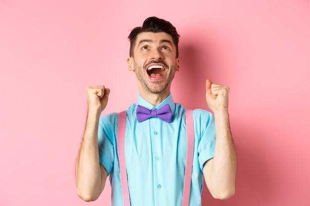 Uomo sollevato e felice che ringrazia dio, alzando lo sguardo in cielo mentre celebrava la vittoria, vincendo il premio e tifando, trionfando su sfondo rosa.