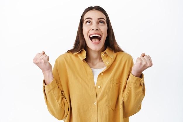 Donna sollevata che vince, celebra la vittoria, ringrazia dio e alza lo sguardo con piacere e felicità, stringe i pugni, trionfa mentre celebra la vittoria, esulta, in piedi sul muro bianco