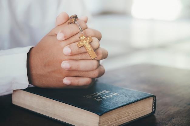 Religione, cristianesimo, preghiera. uomo che prega, mani giunte insieme sulla sua bibbia.