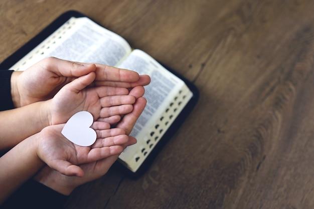 Ragazza cristiana religiosa che prega con sua madre all'interno. bibbia in sottofondo. aveva in mano un cuore di carta bianca. spazio per il testo