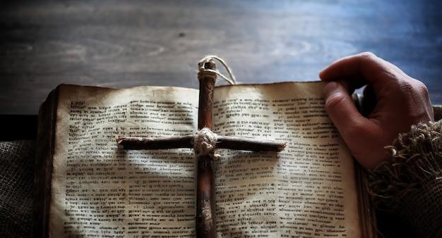 Vecchio libro religioso su una tavola di legno. una croce religiosa legata con una corda e una tela accanto alla bibbia. adorazione, peccati e preghiera.