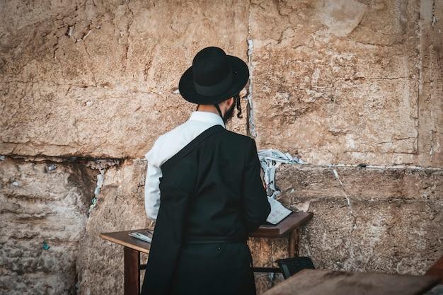 Ebreo ortodosso religioso che prega al muro occidentale e legge la torah nella città vecchia di gerusalemme. ebrei ortodossi