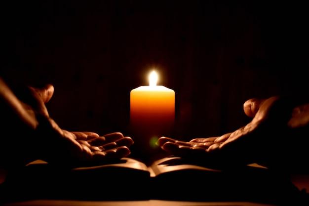 Preghiera religiosa con una candela in completa oscurità.
