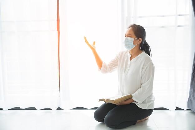 Donna religiosa in maschera protettiva e pregando dio per aiuto a casa. preghiera cristiana ragazza in maschera medica. coronavirus (covid-19