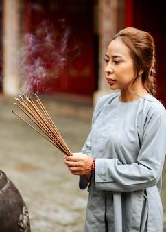 Donna religiosa con incenso che brucia al tempio