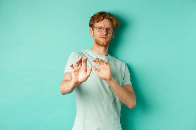 Riluttante uomo dai capelli rossi con gli occhiali che alza le mani in segno di rifiuto, fa un passo indietro, evitando qualcosa con la faccia disgustata e non divertita, in piedi su sfondo turchese.