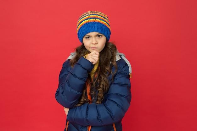 Riluttante a fare qualcosa. bambino dubbioso premuroso. bambina indossare abiti invernali sfondo rosso. concetto di infanzia. cappello lavorato a maglia capelli lunghi ragazza emotiva. stile casual da ragazza teenager. emozioni e umore.