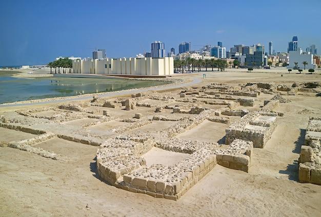 Resti della struttura del forte del bahrain con il paesaggio urbano moderno di manama sullo sfondo manama bahrain