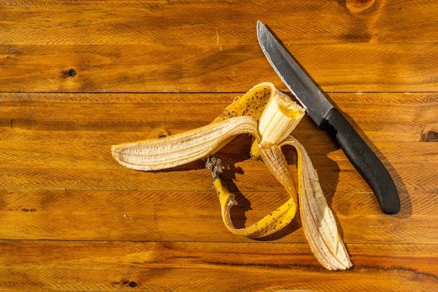 Resti di una banana matura su alcune tavole di legno accanto a un coltello. cibo salutare