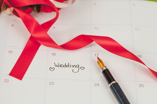Promemoria giorno delle nozze nella pianificazione del calendario e penna stilografica con tonalità di colore.