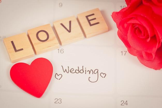 Promemoria giorno delle nozze nella pianificazione del calendario e lettera d'amore su legno con tonalità di colore.