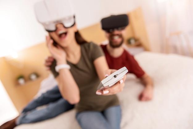 Telecomando. una coppia attraente e allegra che indossava cuffie vr mentre l'uomo metteva la mano sulla spalla della donna e sorrideva
