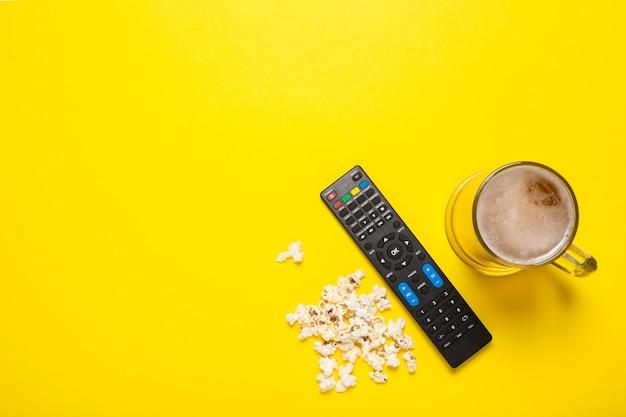 Telecomando da un sintonizzatore tv o tv, un bicchiere di birra e popcorn su giallo