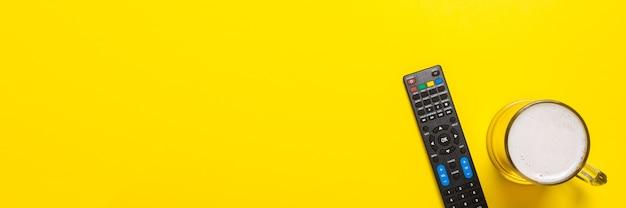 Telecomando dal sintonizzatore tv o tv, un bicchiere di birra sul giallo