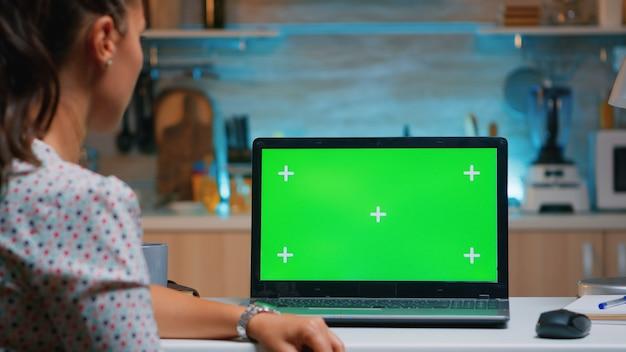 Impiegato remoto che guarda il chroma key seduto nella cucina di casa a tarda notte. donna d'affari che guarda il display del laptop desktop con mockup verde, schermo, durante le ore notturne facendo gli straordinari.