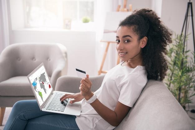 Lavoro remoto. bella donna intelligente che lavora online e riceve il suo stipendio sulla carta di credito