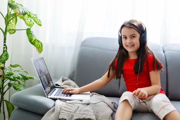 Lezioni a distanza. il bambino sorride felice e acquisisce conoscenza a distanza. la bambina studia l'apprendimento online da casa con il computer portatile. scuola in linea.