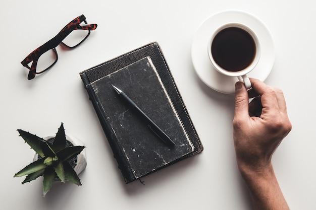 Luogo di lavoro remoto con mano di uomini, tastiera, tazza di caffè e blocco note.
