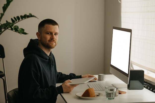 Studio remoto online. uno studente felice studia da remoto usando un computer all-in-one. un compagno che studia con un tablet da casa.