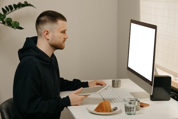 Studio remoto online. uno studente studia da remoto utilizzando un computer all-in-one. un compagno che studia con un tablet da casa.