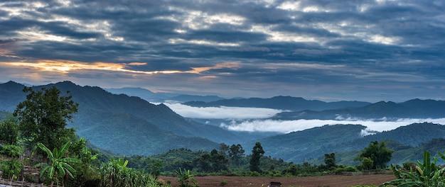 Valle remota nelle montagne del cielo drammatico del tramonto del laos del nord